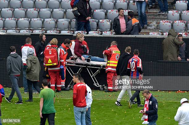Paramedics carry a injured woman off the pitch after the German first division Bundesliga football match between FC Bayern Munich and Hannover 96 in...