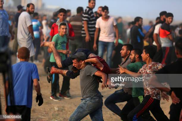 Paramedics carry a wounded Palestinian protester during clashes east of Gaza city along the GazaIsrael border in the Gaza Strip on October 5 2018