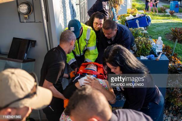 Paramedics carry away a patient on a stretcher that was injured after a earthquake hit the island in Ponce Puerto Rico on January 7 2020 A strong...