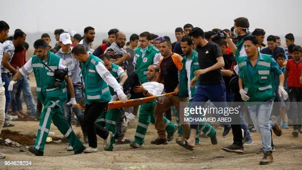 Paramedics carry away an injured Palestinian protester on a stretcher during clashes with Israeli forces along the border with the Gaza strip east of...