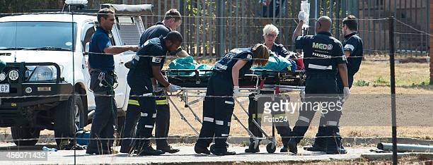 Paramedics carry Tsenolo Rasello into an ambulance on September 21 2014 in Rustenburg South Africa Rescue workers struggled for two days to save a...
