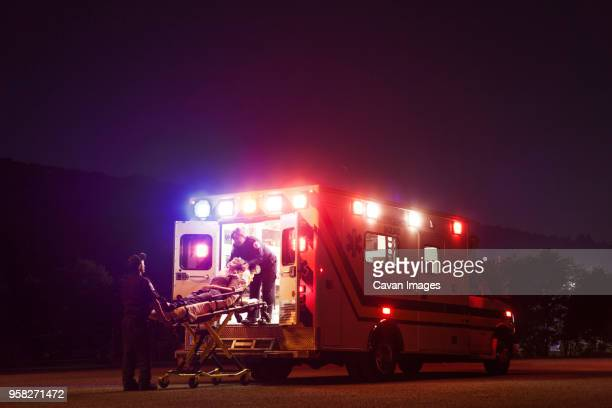 Paramedics carrying patient in ambulance at night