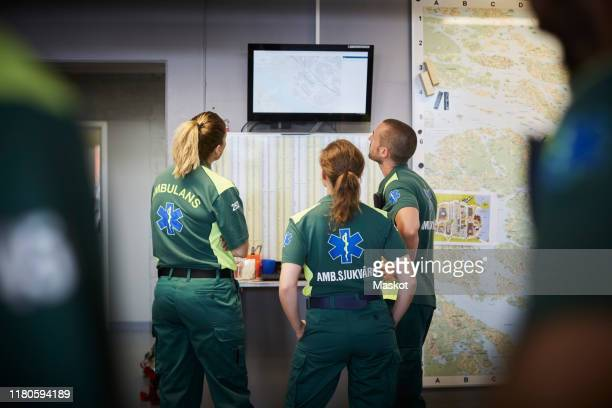 paramedics discussing while looking at screen in hospital - rescue worker stock pictures, royalty-free photos & images