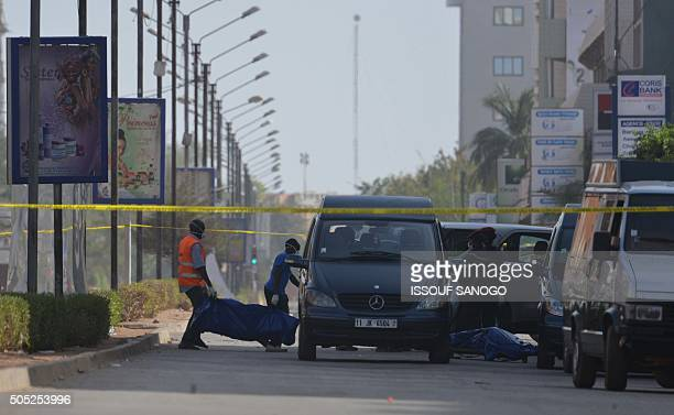 Paramedics evacuate a body outside the Splendid hotel and the Cappuccino restaurant following a jihadist attack in Ouagadougou on January 16 2016 At...