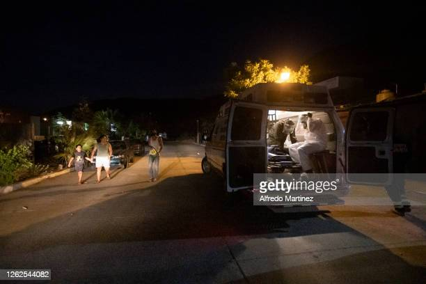 Paramedics from the Calafia group arrive at a house to deliver a food pantry to a family with a COVID-19 positive member on July 28, 2020 in La Paz,...