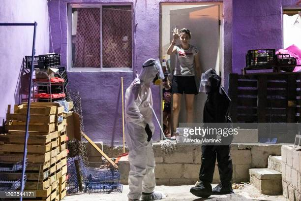 Paramedics from the Calafia group wearing PPE deliver a food pantry to a woman whose son has COVID-19 on July 28, 2020 in La Paz, Mexico. Many...