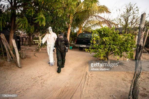Paramedics from the Calafia group wearing PPE leave a house after delivering a food pantry to a family with a COVID-19 positive member on July 28,...