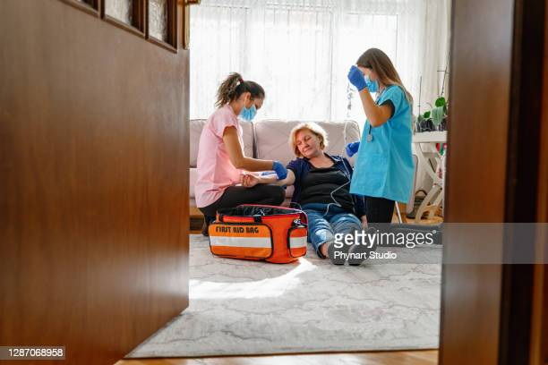 paramedics give first aid to an unconscious elderly woman - first aid kit stock pictures, royalty-free photos & images