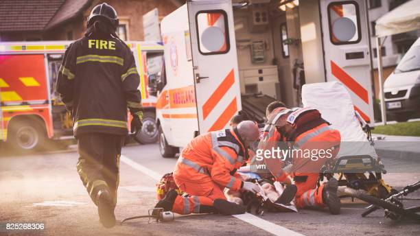 paramedics helping injured cyclist - emergencies and disasters stock pictures, royalty-free photos & images