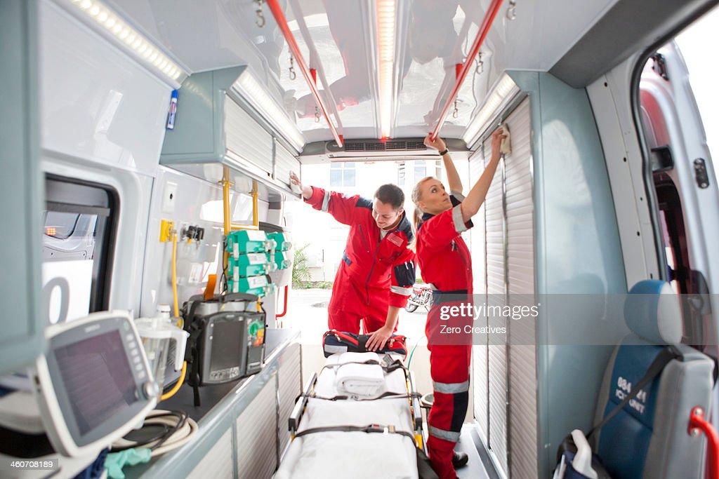 Paramedics in ambulance preparing medical equipment : Stock Photo