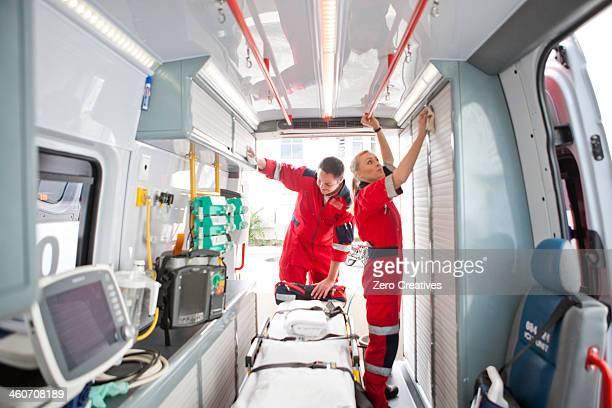 Paramedics in ambulance preparing medical equipment