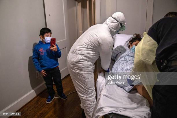EMS paramedics in PPE deliver Zully a COVID19 patient new mother and Guatemalan asylum seeker to her home as her son Junior videos the event on April...