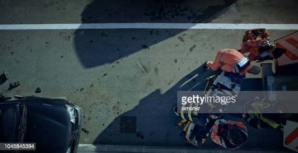 paramedics lifting injured man on stretcher and preparing him for transport - car accident stock pictures, royalty-free photos & images