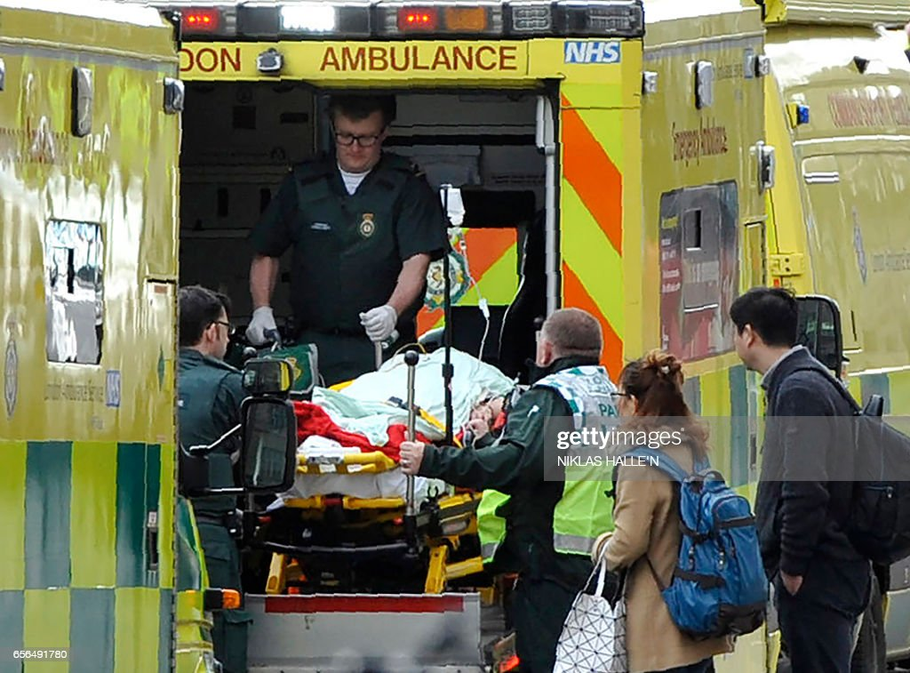 TOPSHOT - Paramedics load a victim into the back of an ambulance as members of the emergency services work on Westminster Bridge, alonside the Houses of Parliament in central London on March 22, 2017, during an emergency incident. British police shot a suspected attacker outside the Houses of Parliament in London on Wednesday after an officer was stabbed in what police said was a 'terrorist' incident. / AFP PHOTO / NIKLAS HALLE'N