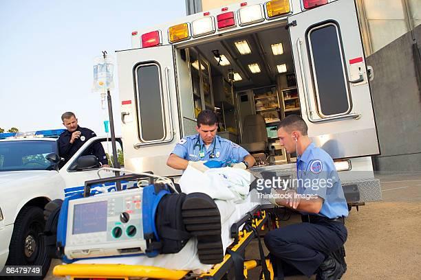 paramedics loading patient into ambulance - 救急救命士 ストックフォトと画像