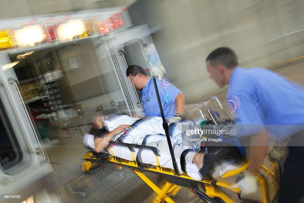 Paramedics loading patient into ambulance : Stock Photo