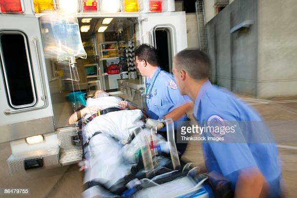 paramedics loading patient into ambulance - paramedic stock pictures, royalty-free photos & images
