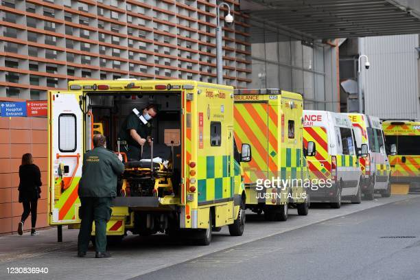 Paramedics move a patient from a ambulance to the Royal London Hospital in east London on January 28, 2021. - Britain on January 26 became the first...