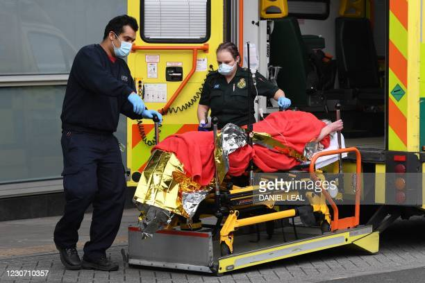 Paramedics move a patient on a stretcher from an ambulance into the Royal London Hospital in east London on January 21, 2021. - Britain's coronavirus...
