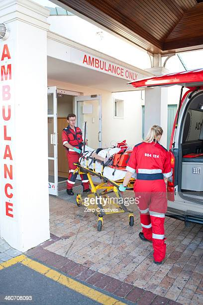 Paramedics moving patient through hospital doorway