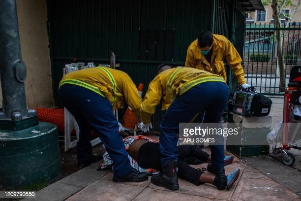 TOPSHOT Paramedics of the LAFD Station No9 perform an ECG test on an unidentified homeless woman who died of unknown causes at Skid Row on April 12...