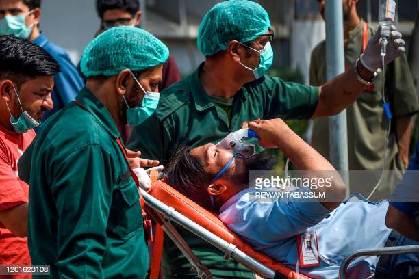 Paramedics personnel shift a patient on a stretcher into the hospital in Karachi on February 18 after a toxic gas leak in a coastal residential area...