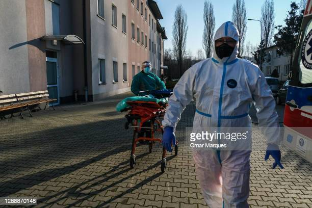 Paramedics prepare a stretcher to transfer a 91 years old woman with coronavirus symptoms from a nursery house to the emergency ward of Bochnia...