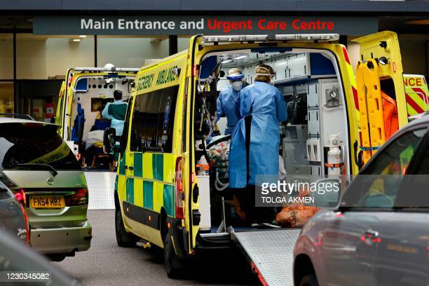 Paramedics prepare to remove a patient from an ambulance parked outside Guy's Hospital in London on December 29 as a new strain of the coronavirus...