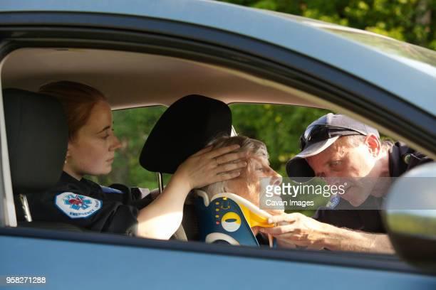 Paramedics putting neck brace on patient in car