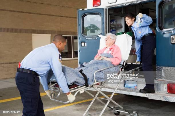 paramedics putting senior woman into ambulance - hospital gurney stock pictures, royalty-free photos & images