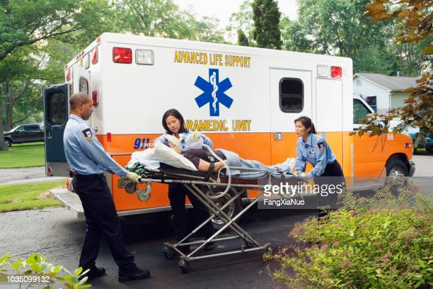 paramedics putting woman into ambulance - rescue services occupation stock pictures, royalty-free photos & images