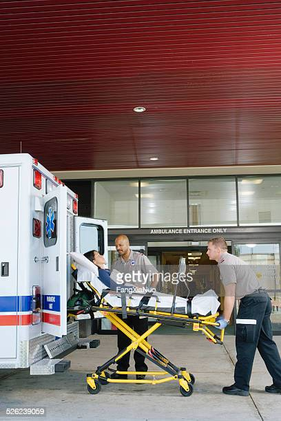Paramedics removing patient on stretcher from ambulance