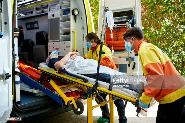 paramedics removing senior man from ambulance on stretcher - pandemic illness stock pictures, royalty-free photos & images
