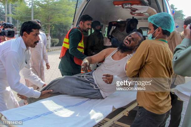 Paramedics shift an injured victim to a hospital in Multan on October 31 after a passenger train caught on fire near Rahim Yar Khan in Punjab...