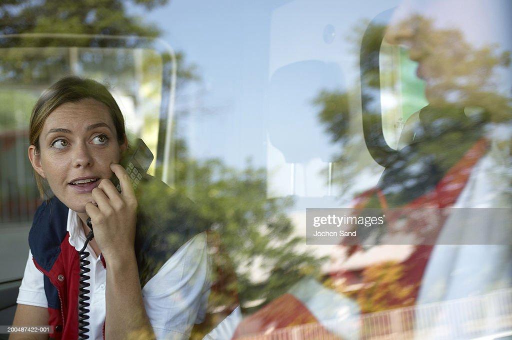 Paramedics sitting in ambulance, female using telephone : Stock Photo