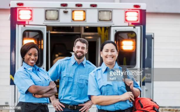 paramedics standing at the rear doors of an ambulance - rescue services occupation stock pictures, royalty-free photos & images
