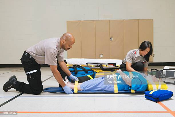 Paramedics strapping patient to stretcher in gymnasium