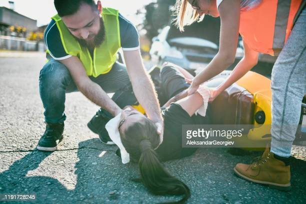 paramedics supporting female's head to avoid neck injury after accident - gory car accident photos stock pictures, royalty-free photos & images
