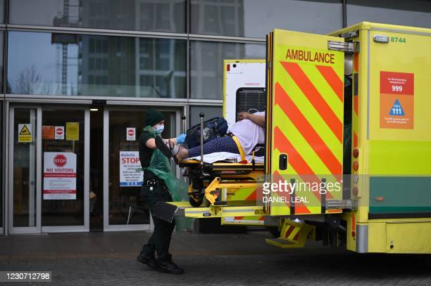 Paramedics take a patient out of their ambulance and into the Royal London Hospital in east London on January 21, 2021. - Britain's coronavirus...