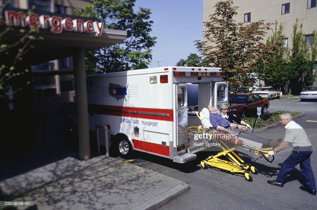 Paramedics taking patient on gurney from ambulance at emergency ward : Stock Photo