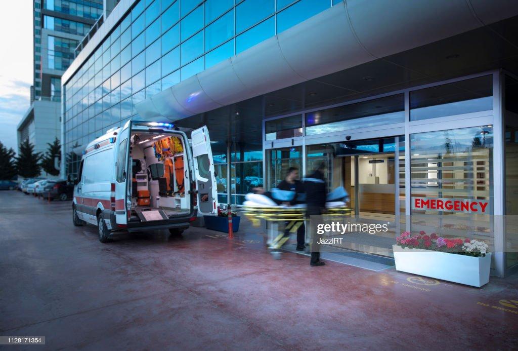 Ambulanspersonal tar patienten på bår från ambulansen till sjukhuset fortkörning ambulans, (suddig motion) : Bildbanksbilder