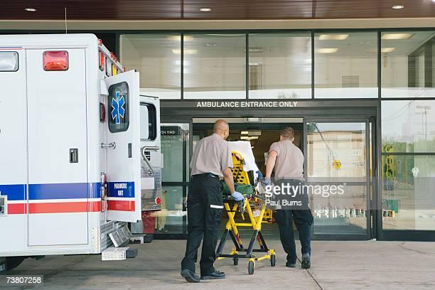 paramedics taking patient on stretcher from ambulance to hospital - rettung stock-fotos und bilder