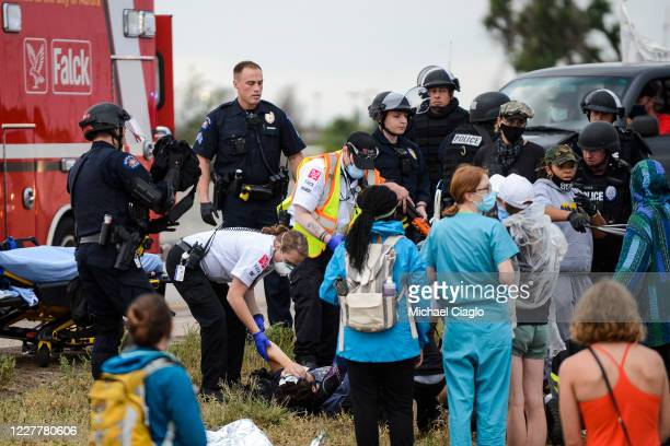 Paramedics tend to a man who was shot while a car sped through a crowd of protestors marching on I225 to protest the death of Elijah McClain on July...