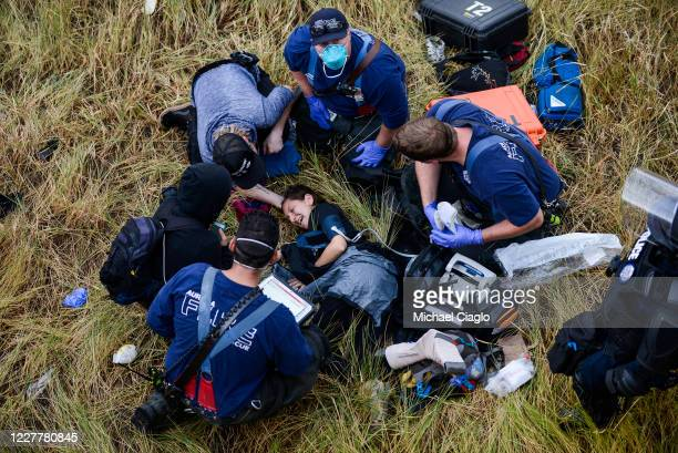 Paramedics tend to a woman who jumped off the side of the highway to avoid a car speeding through a crowd of protestors marching on I225 to...