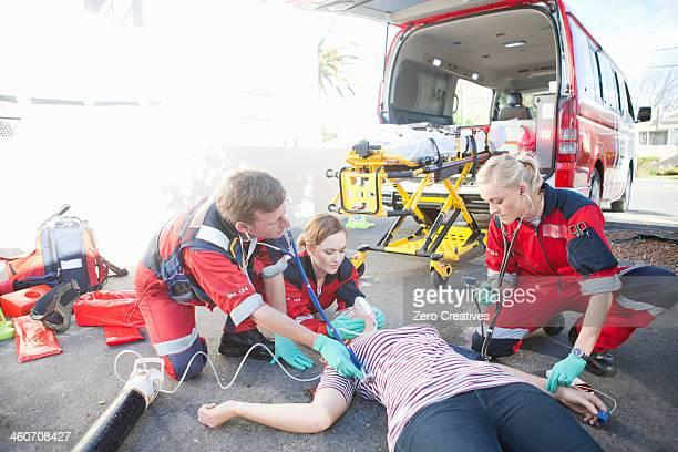 Paramedics tending patient lying on road