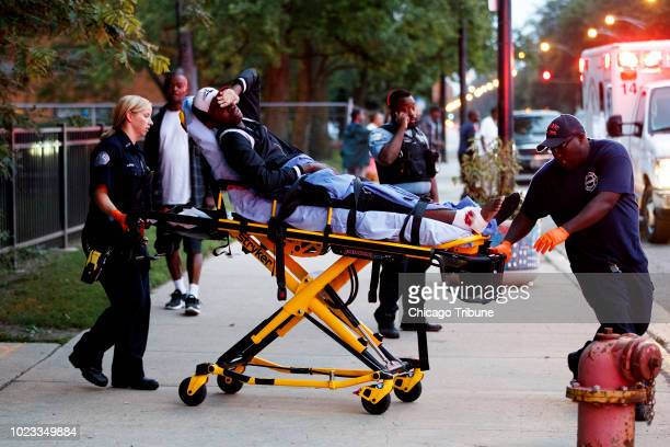 Paramedics transport a 17yearold who was shot in the ankle at the scene where two 17yearolds were shot in the ankle and a 21yearold man was shot in...