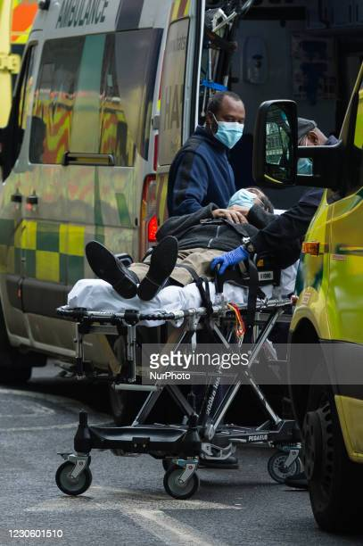 Paramedics transport a patient to the ambulance outside the emergency department at the the Royal London Hospital, on 15 January, 2021 in London,...