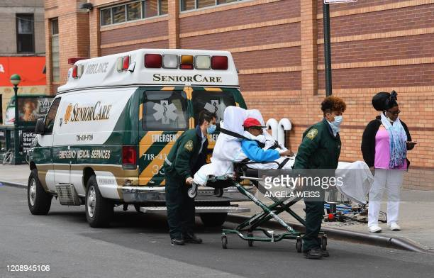 Paramedics transport a patient to the emergency room entrance of the Wyckoff Heights Medical Center in Brooklyn on April 02 2020 in New York