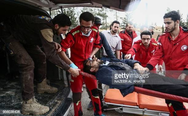 Paramedics transport an injured Syrian into an ambulance from a gurney upon arriving at Abu alZandin checkpoint near alBab in northern Syria on May 8...