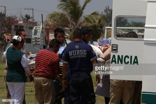 Paramedics transport Mexican journalist Armando Arrieta Granados seriously injured after being attacked by armed men outside his house in Poza Rica...